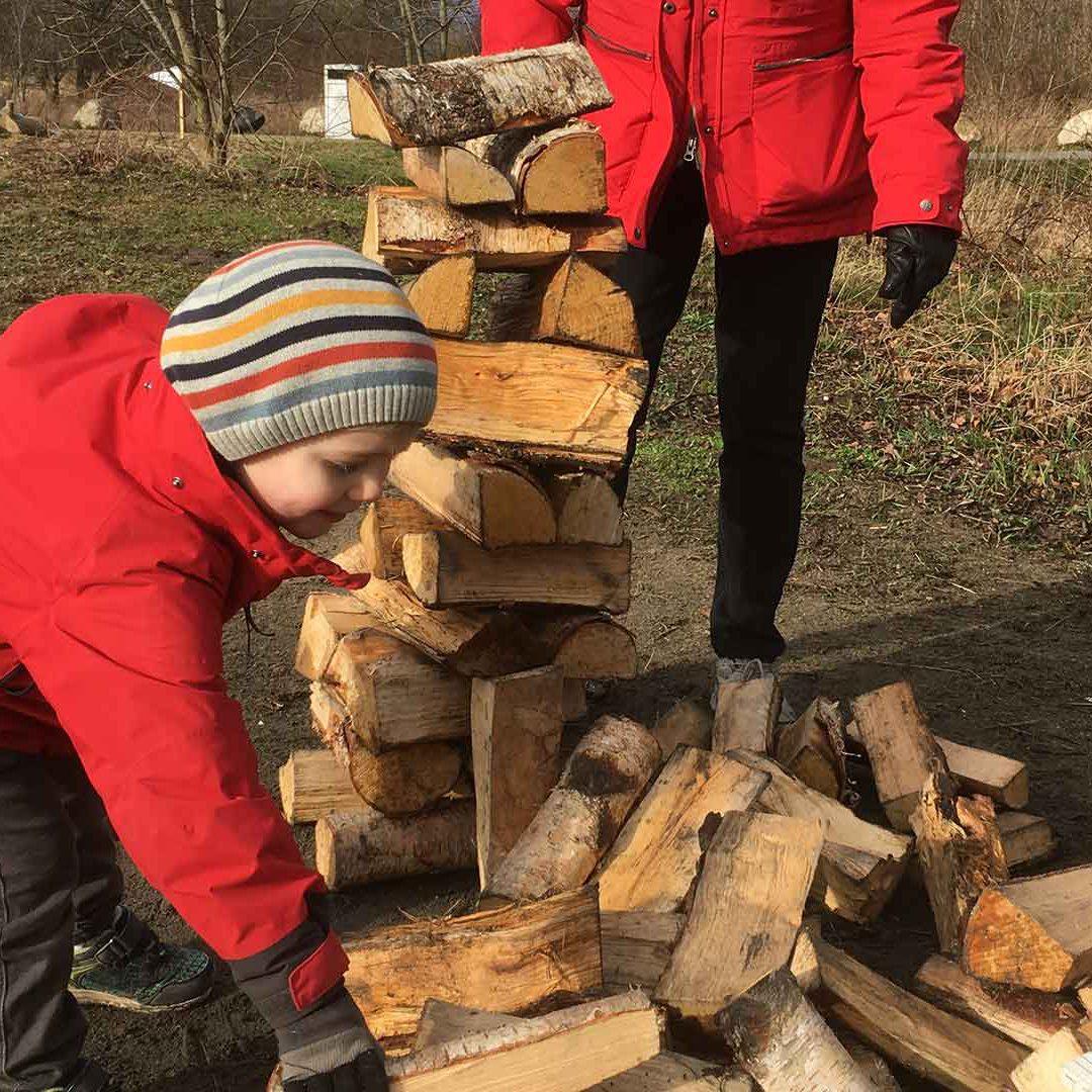 Barn sträcker sig efter ett vedträ dör att bygga ett högt torn.