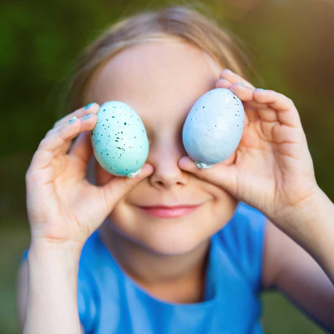 Flicka som håller två ägg framför ögonen