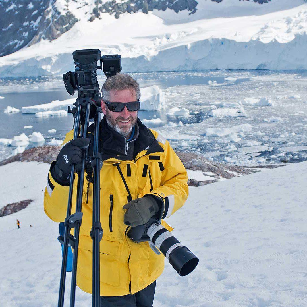 Patrik Olofsson står i gul jacka bland snö och is på Antarktis med filmkamera