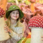 Två flickor med svamphattar håller varsin flugsvamp i tyg