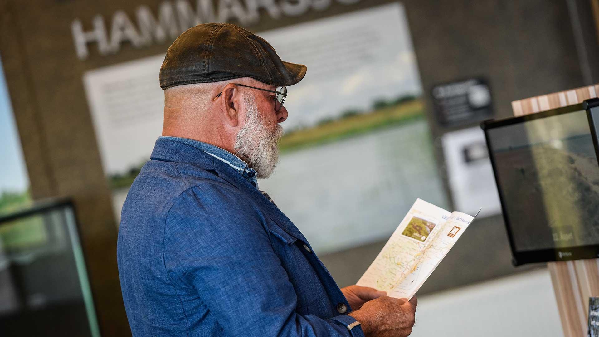 Man läser en broschyr på naturum. Foto Jennie Ahlqvist