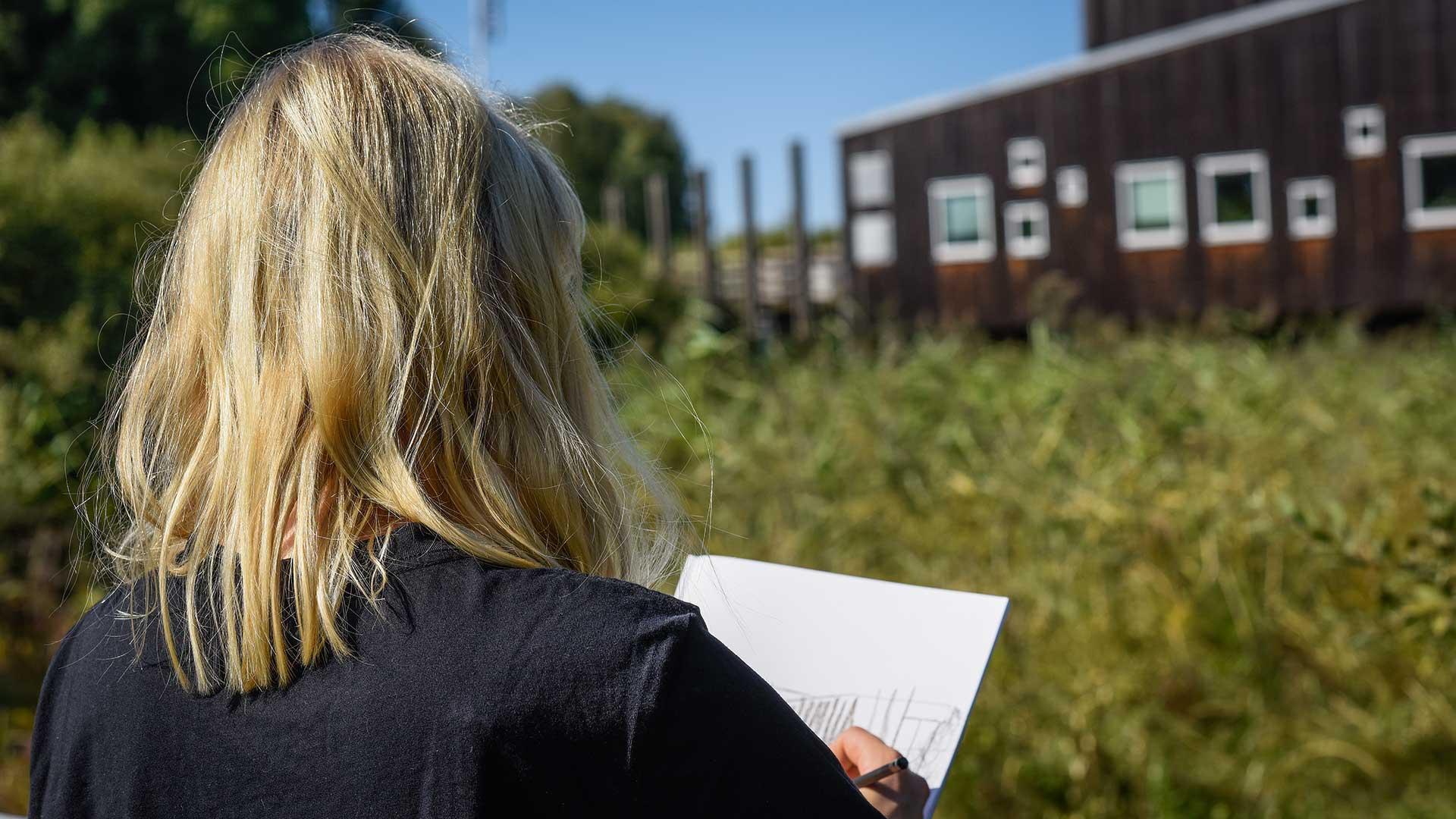 En tjej står på spången och tittar mot naturum. Foto Jennie Ahlqvist