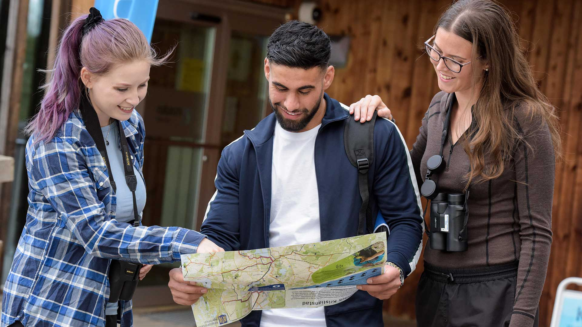 Tre personer tittar tillsammans på en karta utanför naturum